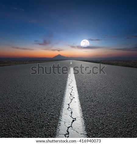 Empty highway leading to the mountains through the desert against the rising full moon at night. - stock photo
