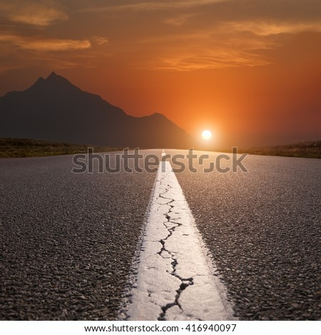 Empty highway leading to the mountains through the desert against the rising sun at beautiful sunset. - stock photo
