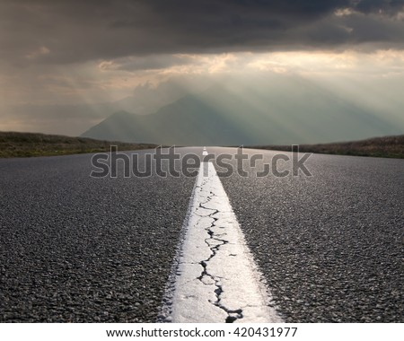 Empty highway leading to the mountains through the desert against the sun rays at beautiful morning. - stock photo