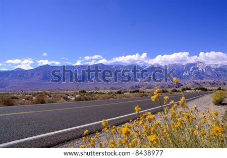 Empty highway with Sierra Mountains backdrop - stock photo