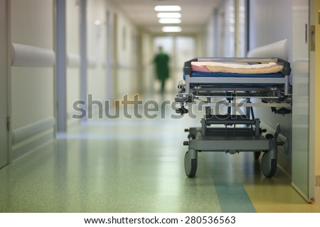 Empty hospital cot in a corridor - stock photo