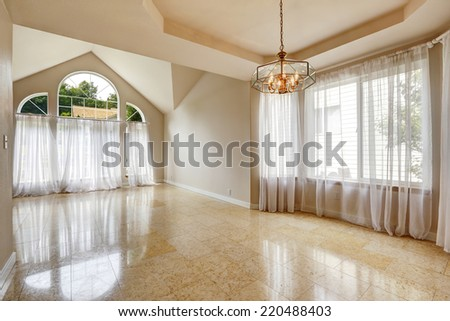 Empty house interior with shiny marble  tile floor. Hight vaulted ceiling with large windows and transparent white curtains - stock photo