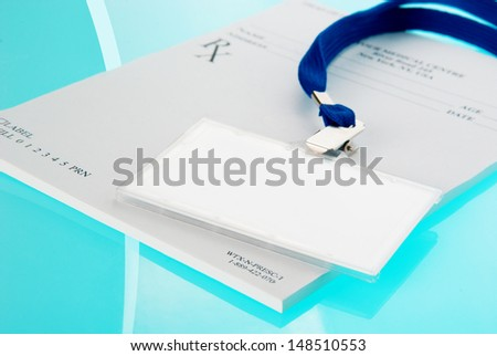 Empty ID tag and medical prescription on blue, reflective background - stock photo