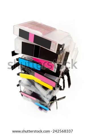 Empty ink cartridges with labels of various colors stacked on white background. Taken with a wide angle lens for greater depth of objects - stock photo