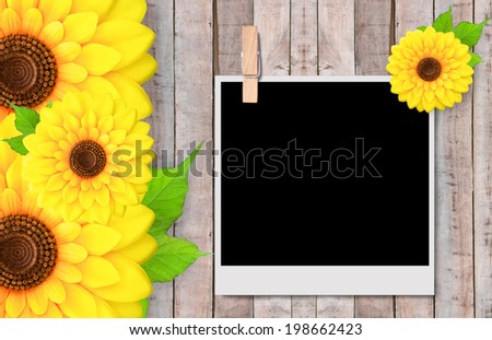 Empty instant photos and sunflowers on old wooden texture - stock photo