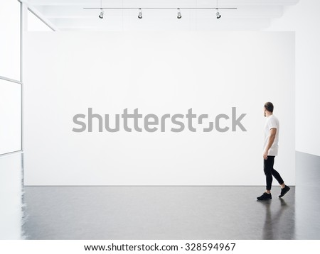 Empty interior with white, blank, canvas and young man.  - stock photo