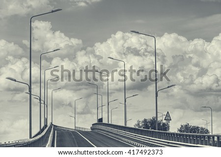 Empty interstate road with highway lamp posts over cumulus clouds in the sky. Monochrome, black and white. - stock photo