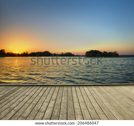Empty jetty and lake surface just after sunrise, Mazury, Poland - stock photo
