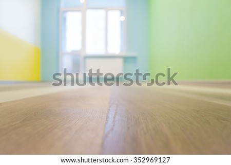 Empty kids room interior background with color walls and wooden flooring, shallow depth of focus - stock photo