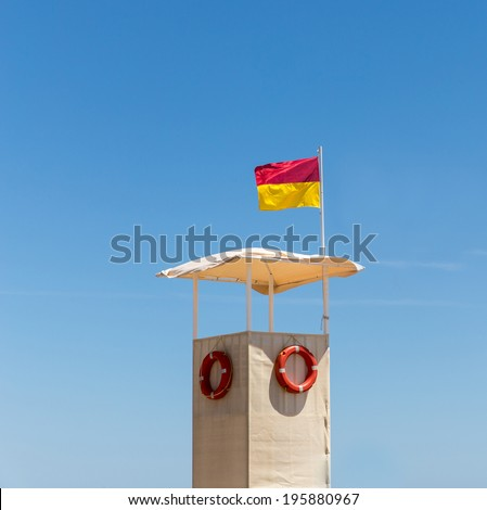 Empty lifeguard booth on the beach with life buoys against a blue sky - stock photo