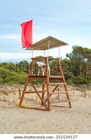 Empty lifeguard tower with red flag on the beach. - stock photo