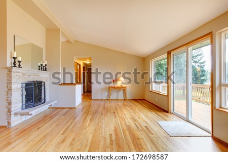 Empty living room with a fireplace, hardwood floor and sliding glass door exit to the deck - stock photo