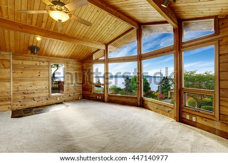 Empty living room with carpet floor in wooden trim house with large windows and balcony door. Water view - stock photo