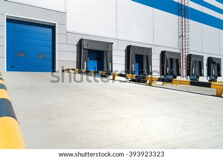 Empty loading dock of large warehouse, entry to warehouse wit yellow separator - stock photo