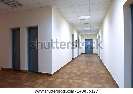 empty long corridor in the modern office building - stock photo