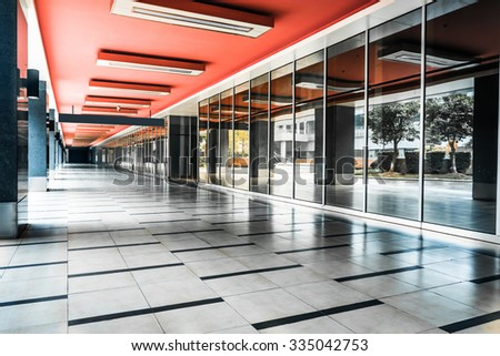 empty long corridor in the modern office building. - stock photo