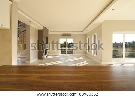 Empty lounge of a modern house, with a table top in the foreground - stock photo
