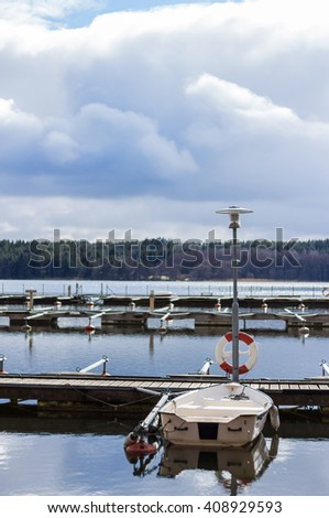 Empty marina waiting for the tourist and boating season to start. Early spring view of mooring with only one boat beside lifebuoy. Beautiful landscape with row of free piers on lake. Sunny cloudy day - stock photo