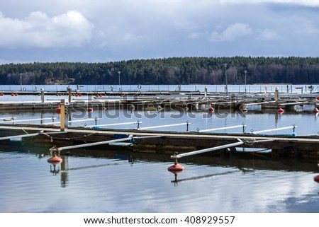 Empty marina waiting for tourist and boating season to start. Early spring view of mooring. Beautiful landscape with row of free piers on lake. Sunny cloudy day. Free parking before flow of visitors - stock photo
