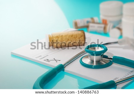 Empty medical prescription with a sthetoscope and medicine bottles  on blue reflective background - stock photo