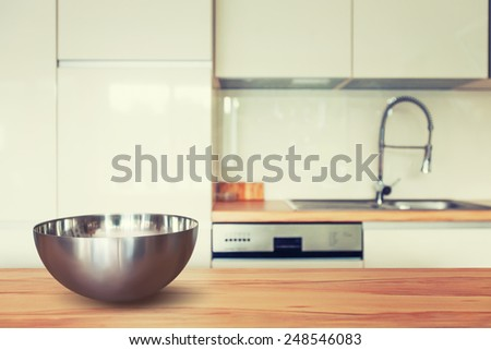 Empty metal bowl on wooden table and modern kitchen space. Toned in warm colors - stock photo