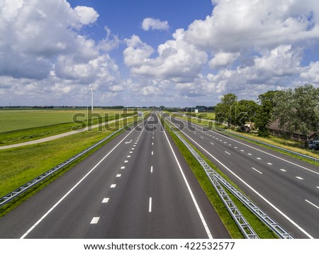 Empty motorway with no traffic apart from far in the distance, in a flat green landscape with a beautiful half cloud sky - stock photo