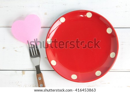 Empty note paper attached to fork and plate, on wooden background - stock photo