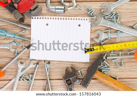 empty note with tools kit on parquet plank - stock photo