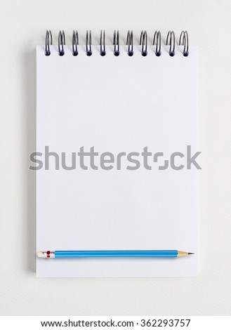 Empty notebook for sketching and blue pencil on white background. - stock photo