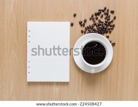 Empty notebook sheet with coffee cup and coffee beans on wooden background. - stock photo