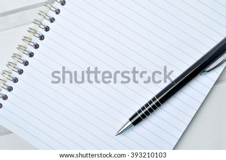 Empty notebook with pen on table - stock photo