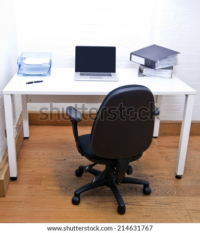 Empty office chair with laptop on desk - stock photo