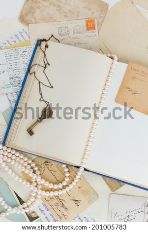 empty old book page with  antique key, postcards and strand of pearls vintage background with copy space - stock photo