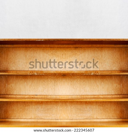 empty old retro wooden book shelf near the stucco wall - stock photo