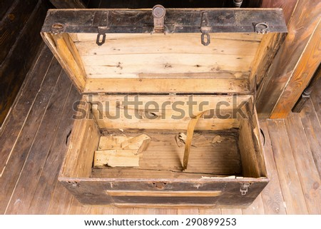 Empty old vintage wooden chest with the lid open standing on a wooden floor , high angle view looking inside - stock photo