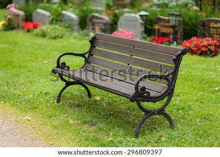 Empty old wooden bench in cemetery - stock photo