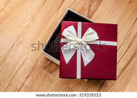 Empty open burgundy gift box with elegant white bow, over wooden background, top view - stock photo