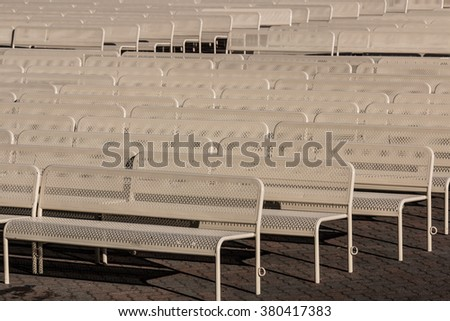 Empty outdoor audience benches in rows facing left. - stock photo