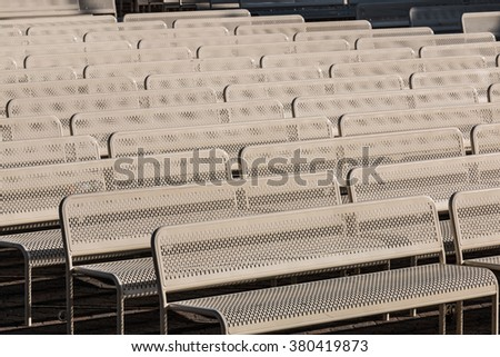 Empty outdoor audience benches in rows facing right. - stock photo