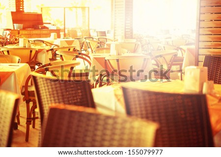 Empty outdoor restaurant tables at sunset - stock photo