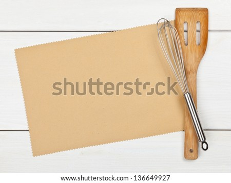 Empty paper for recipe with cooking utensils on kitchen table - stock photo