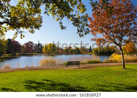 Empty park bench by scenic lake in the fall - stock photo