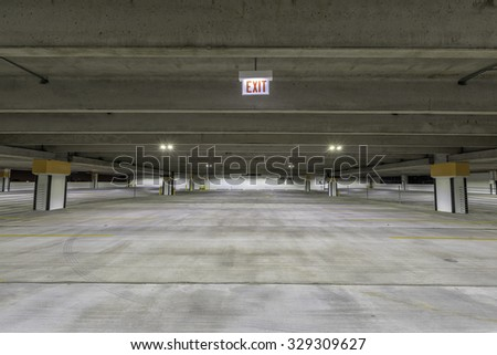 Empty parking garage with exit sign at night - stock photo