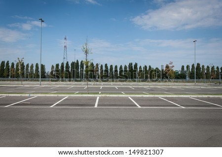 Empty parking lot with trees in the distance - stock photo