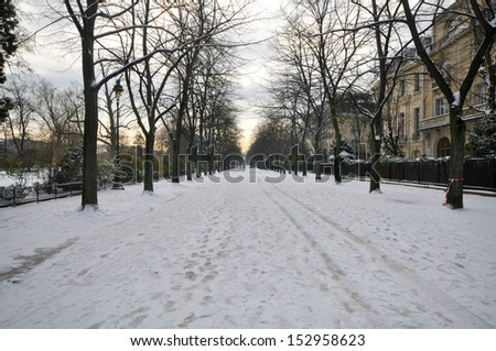Empty path covered in snow on a winter day - stock photo