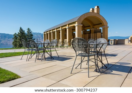 Empty patio table & chairs at a winery inspired by old Tuscany style architecture - stock photo