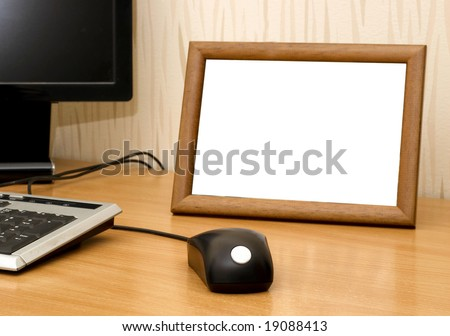 Empty photo frame on computer table - stock photo