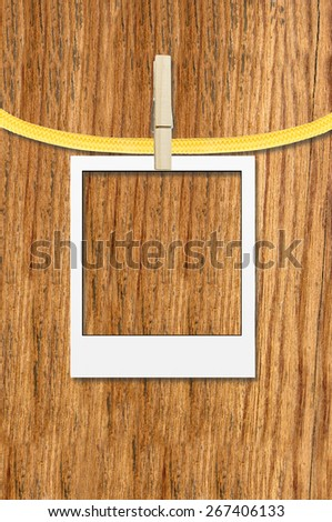 empty photo frame with clothespin over wooden background - stock photo