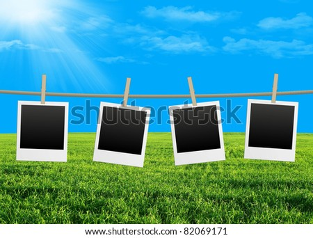 empty photo frames on green field background - stock photo