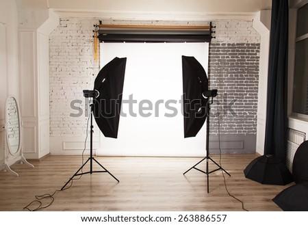 Empty photo studio interior with white background and lighting equipment - stock photo